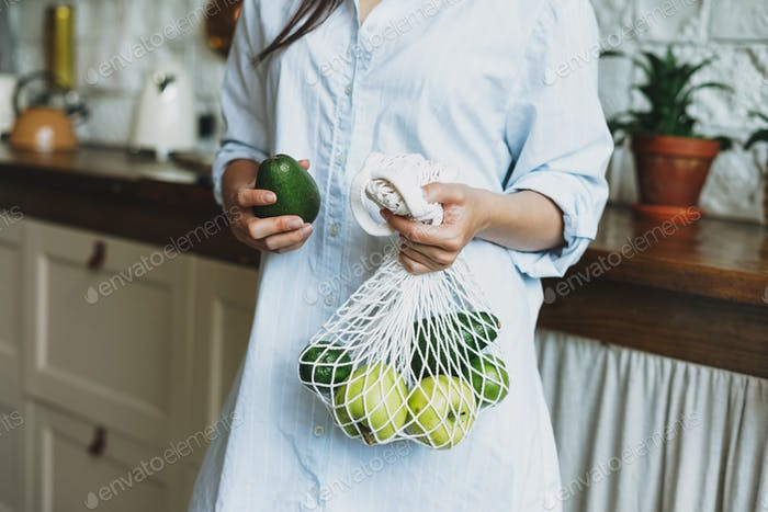 Young woman in shirt hold knitted rag bag shop with avocado and green apples in hands on kitchen