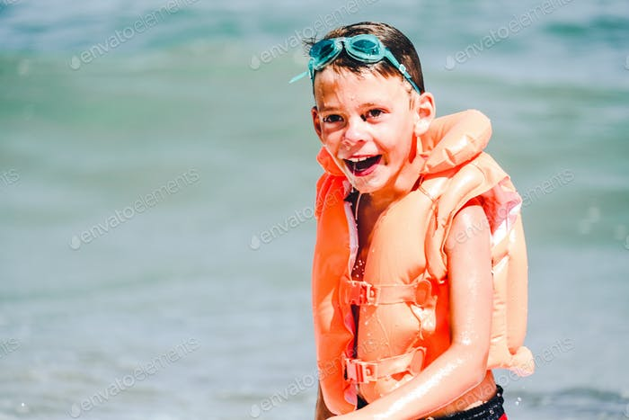 Smiling boy in orange inflatable vest and swimming goggles in the sea