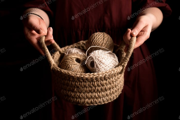 Hands of woman holding jute-knitted basket with balls of jute threads