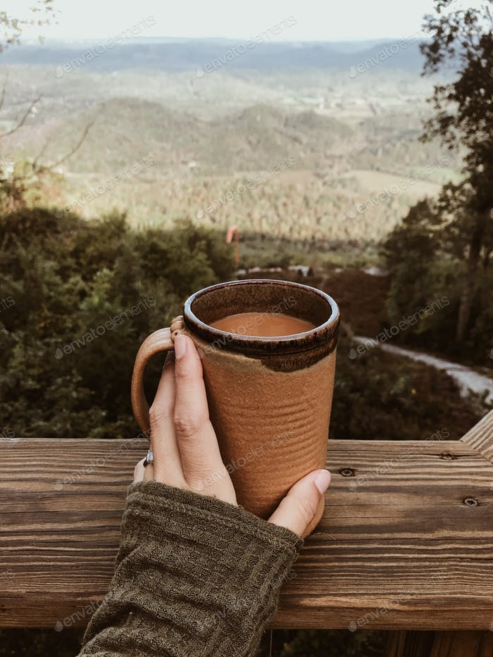 Hand holding a coffee in a stoneware mug on a porch with view of the mountains at a cabin