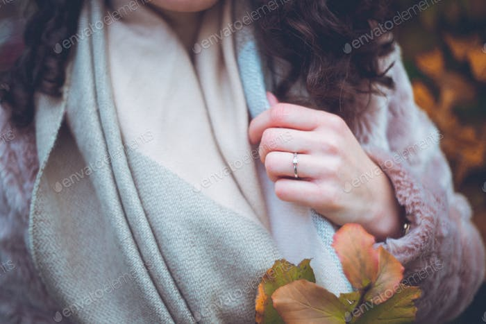 Close up of scarf and furry coat with autumn leaves
