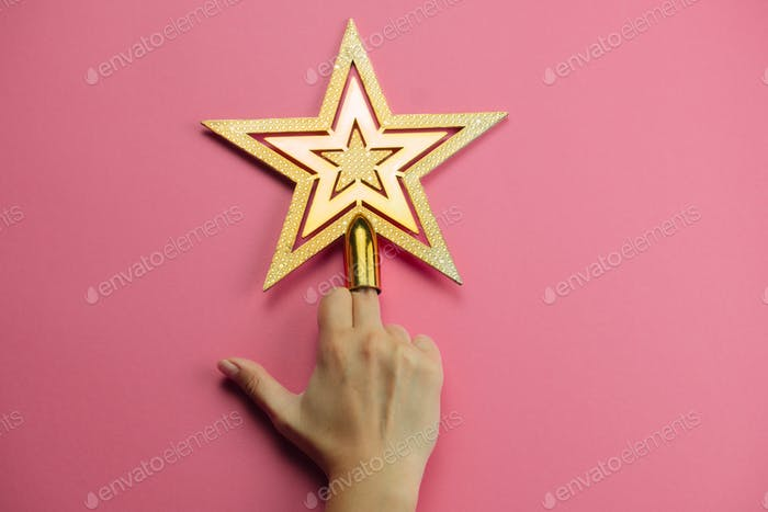female hand showing middle finger decorated with golden star on a pink background