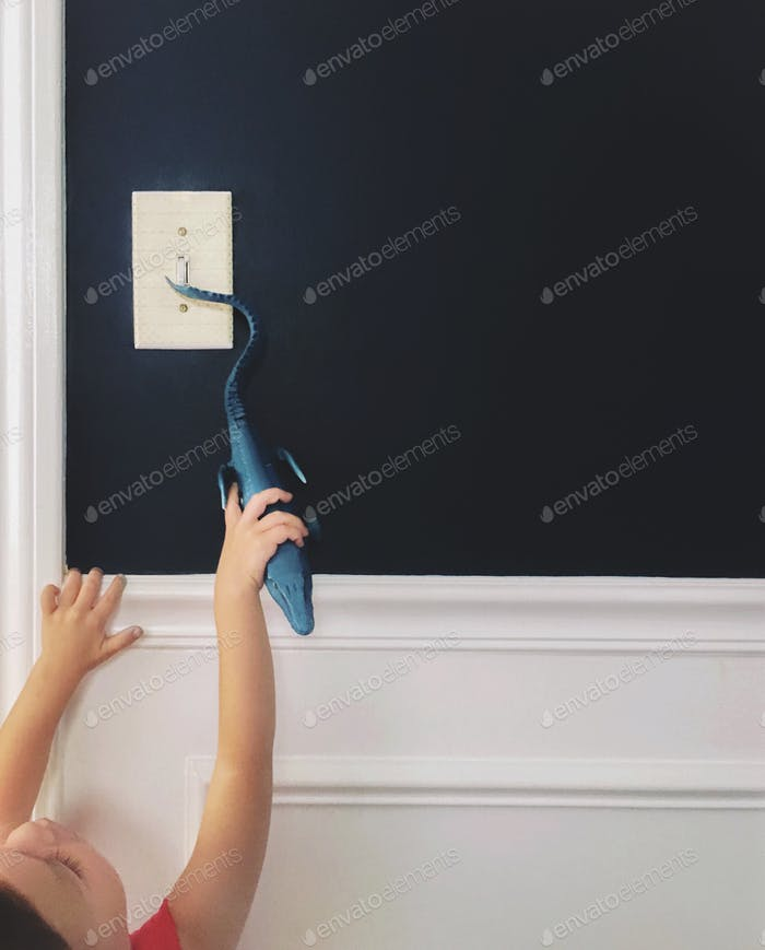 Resourceful young boy using a toy dinosaur to turn on a light switch on a dark wall.