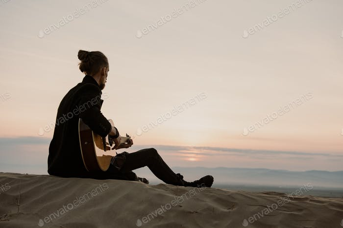bearded hipster playing guitar on a sand hill in the sunset