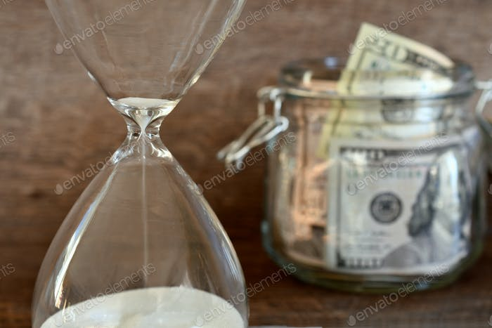 Concept - time running out on saving for retirement - sand in an hourglass with a jar of money cash