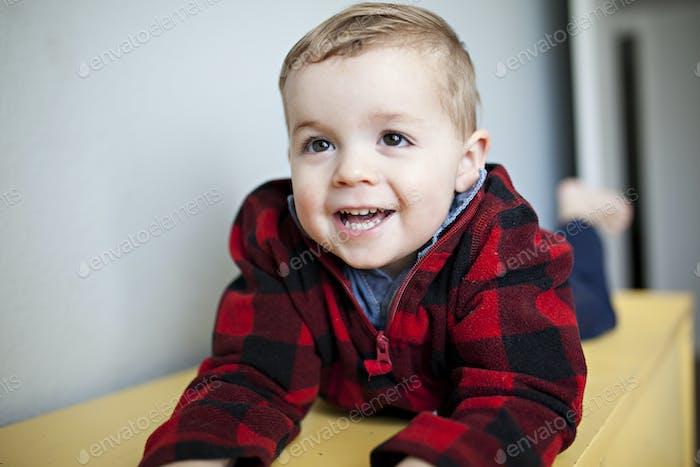 toddler laughing in a lumberjack sweater