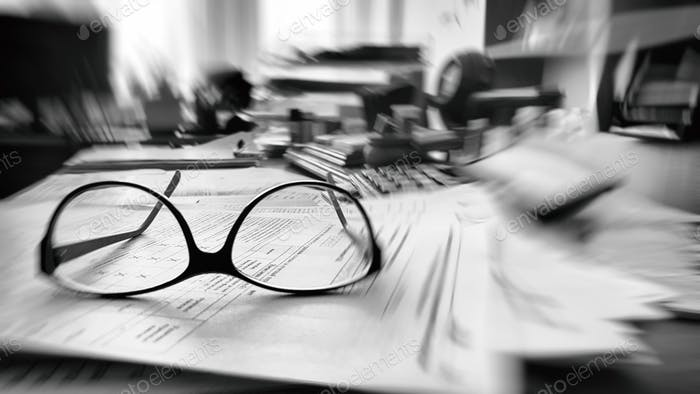 Routine day at the office, messy desk with lot of papers. Black and white.
