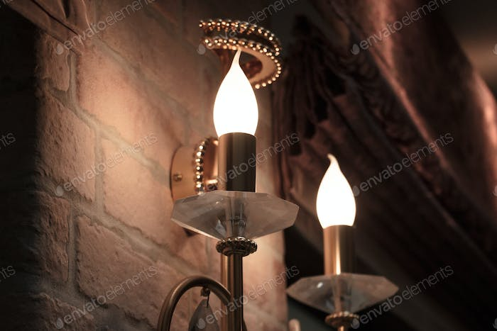 interior design - a light bulb in the form of candles hanging on a brick wall
