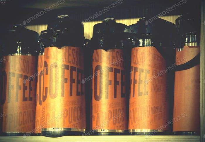 A shelf with coffee carafes in brown.