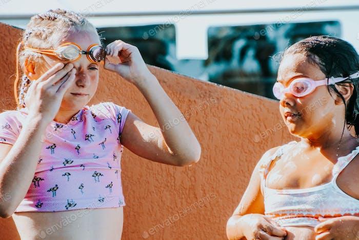junge Schwimmer stehen am Pool mit Schwimmbrille und tropfnass
