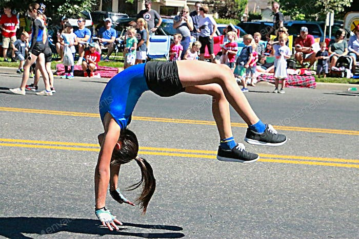 Image of young adult doing back flips in the street during a parade