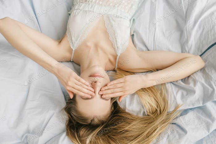 Girl long fair haired is lying on back on light blue bed covering hide face hands
