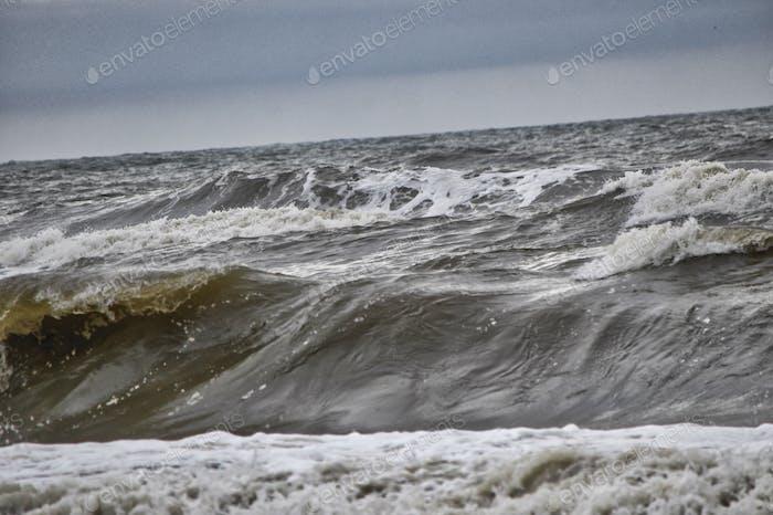 Sturmwellen drehten den Sand vom Meeresboden auf, um schmutzige und braune Wellen zu bringen und