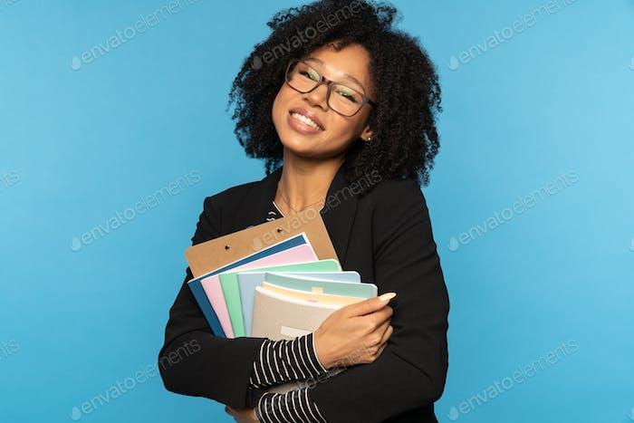 Счастливый студент в блейзере, носить очки, держать тетради, документы и папки, улыбаться, изолировать.