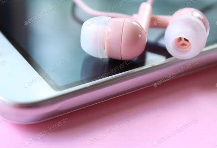 Pink earbuds on cell phone