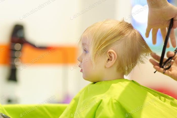 Vorschulkind bekommt Haarschnitt. Kinderfriseur mit professionellen Werkzeugen - Kamm und Schere.