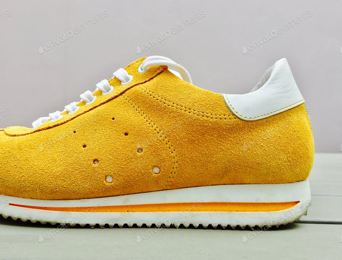Trendy  yellow suede colored ladies sneaker with white laces and yellow, white striped sole. Shoes.
