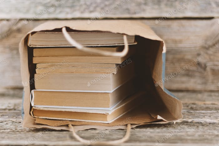 !!Nominated!! Pile of analog vintage book in paper bag on wooden background