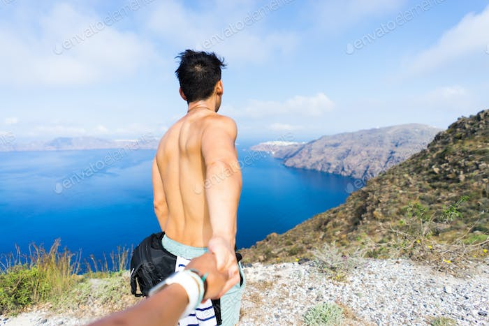 Hiking from Oia to Fira in Santorini, Greece. Holding hands with a view of the ocean and landscape.