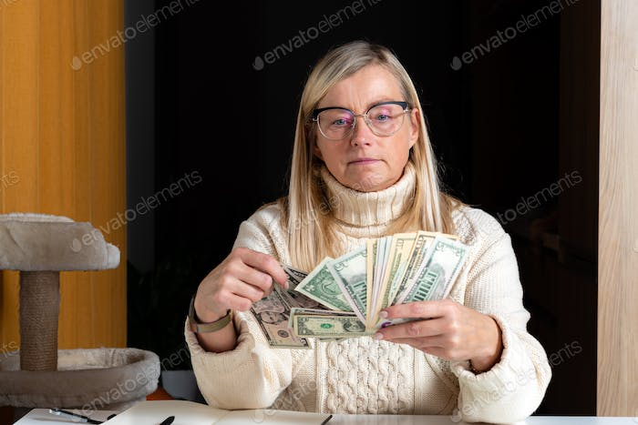 surprised female employee sitting at work and looking at dollar banknotes,  financial welfare concep