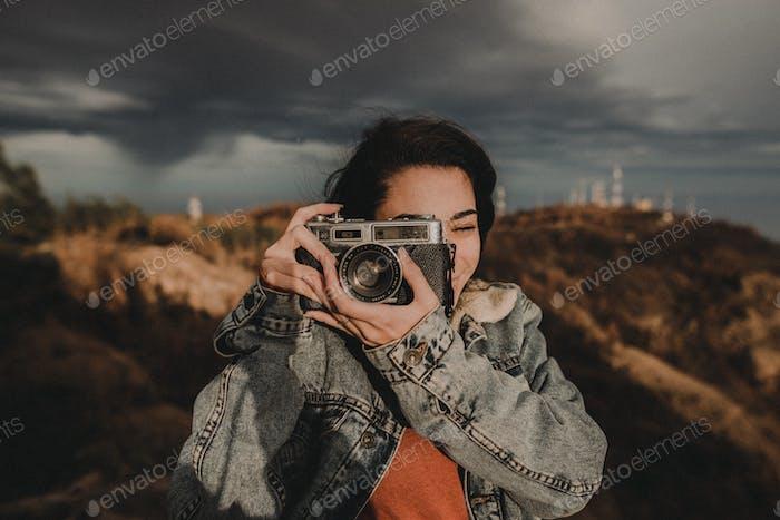 An happy girl with a film vintage camera