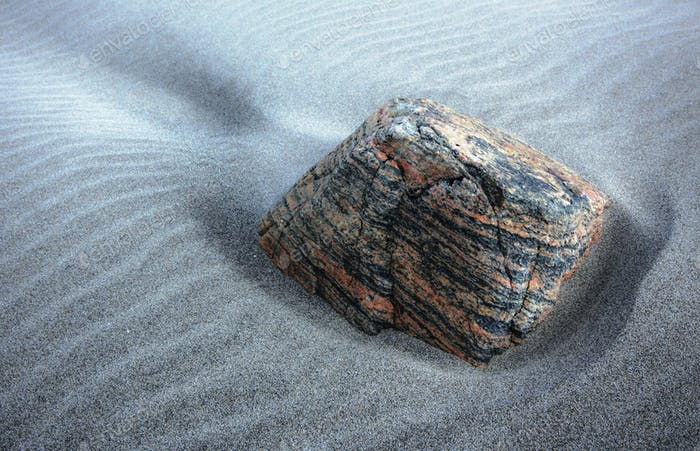 Un trozo de granito en la playa de arena, Isla de Lewis, Escocia