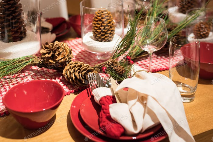 Rustic holiday tabletop with red dishes and pine cones and greenery for holiday entertaining