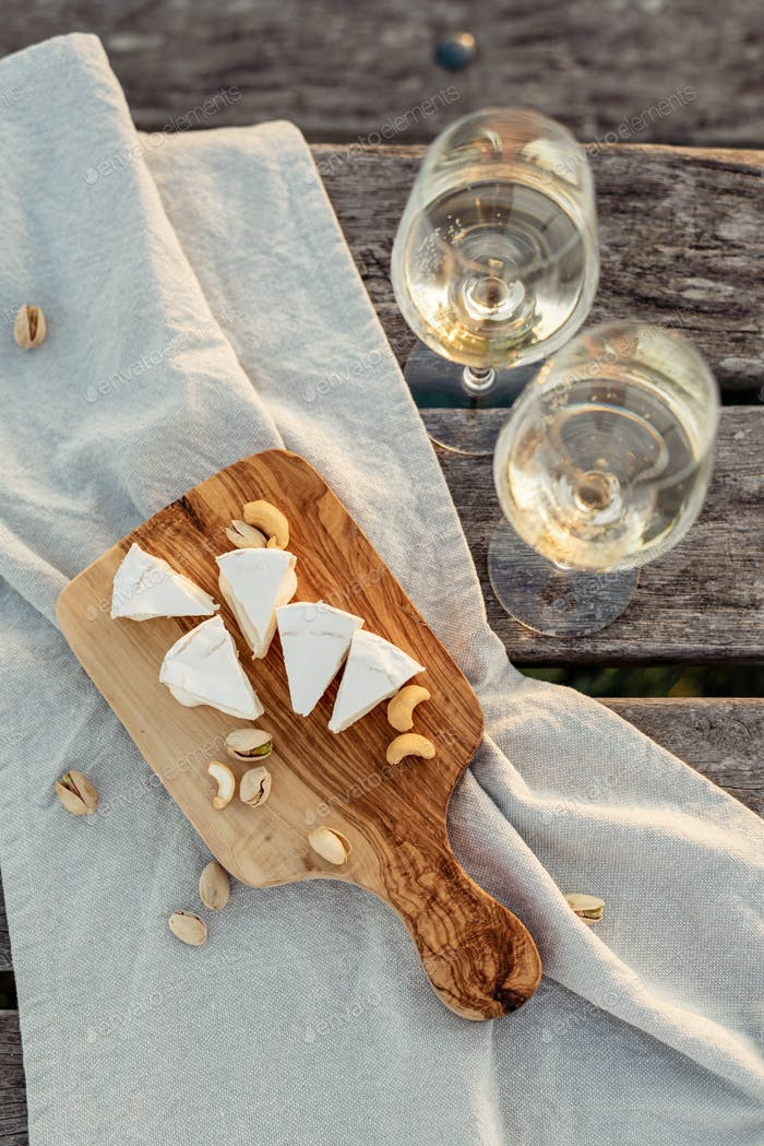 Two glasses of white wine and wooden plate with cheese and nuts during sunset time outside