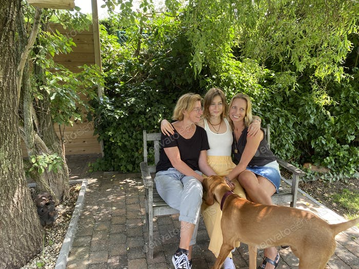 Three young women sitting on a bench posing for a family picture