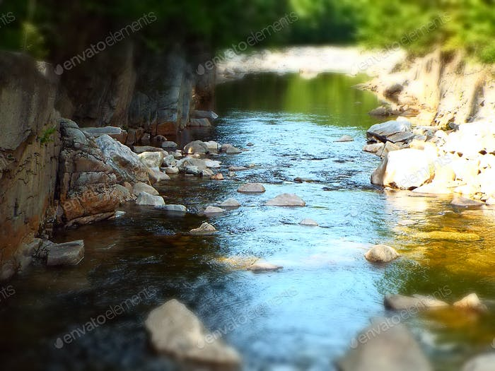 quiet rocky mountain stream with slow moving water and dappled sunlight - miniature effect