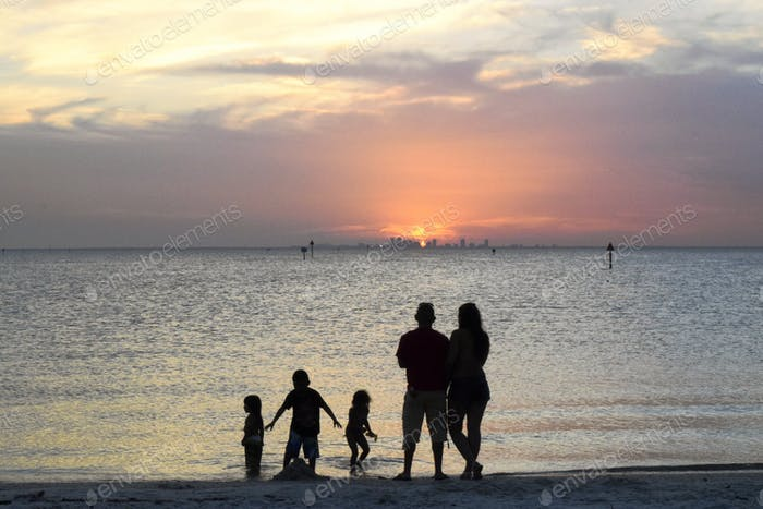 Family playing in the water at a Tampa Bay beach while silhouetted by the sunset over St
