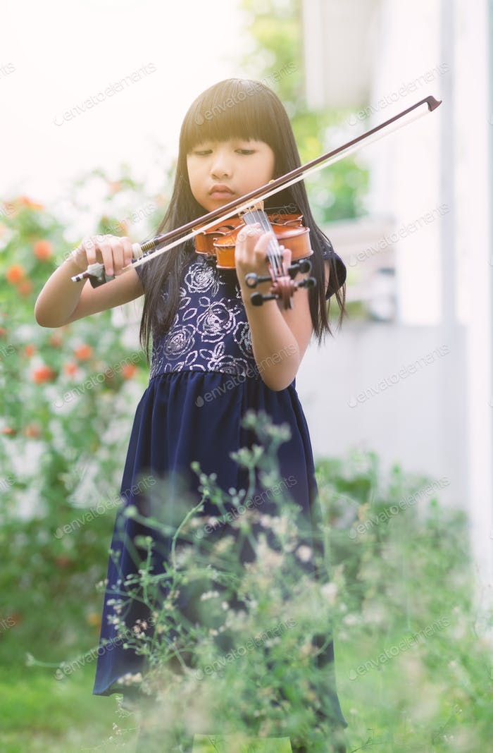 Vertical orientation full length portrait of an Asian cute little girl playing violin in a garden