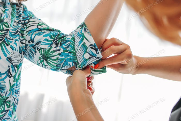 Woman seamstress, stylist or sales consultant buttons on the sleeve of the client
