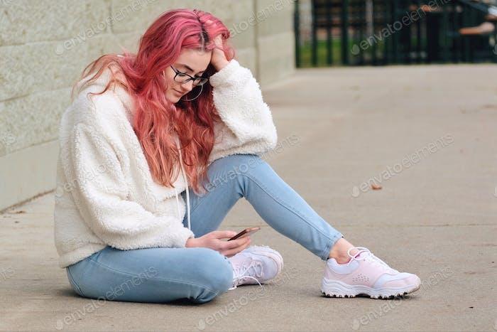 Девушка с розовыми волосами смотрит на свой телефон