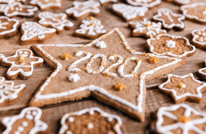 Lebkuchenkekse auf hölzernem Hintergrund, Sternförmiger Cookie mit Nummer 2020. Frohes neues Jahr, neues y
