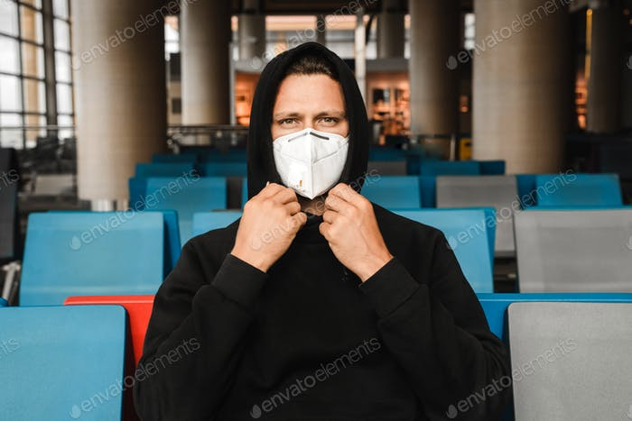 Men in respirator mask N95 sitting at the empty airport terminal