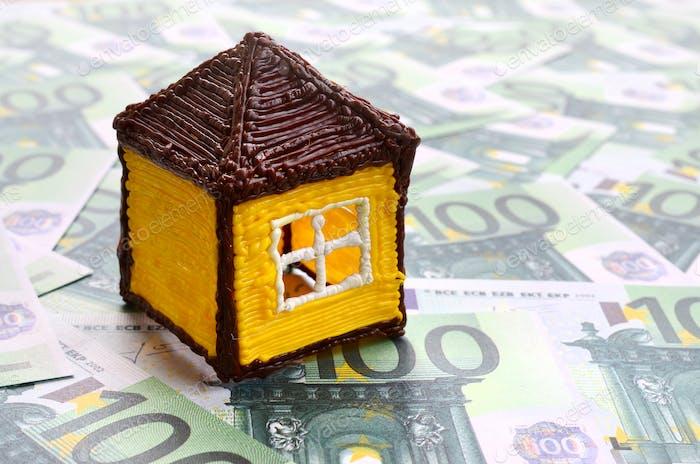 Pequeña casa de juguete se encuentra en un conjunto de denominaciones monetarias verdes de 100 euros
