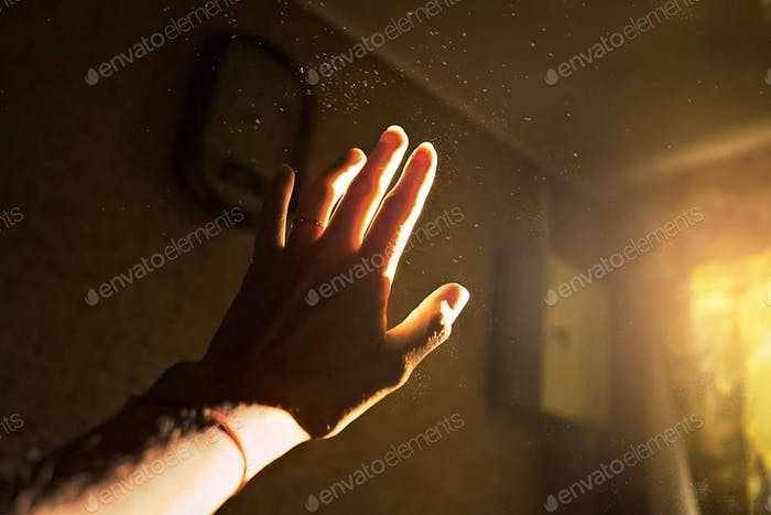 A woman's hand reaches out to the light. Specks of dust in the light. Light and shadow