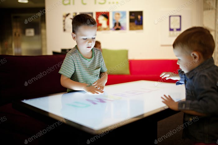 dos chicos jugando en una pantalla táctil gigante tv