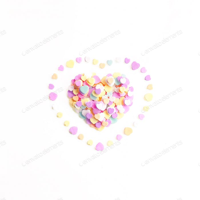 Pastel heart shape formed from candy conversation hearts on white background.