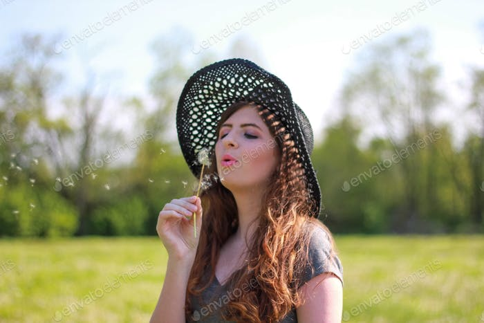 Young woman in stylish black hat blowing dandelion seeds in the wind in a field of greenery