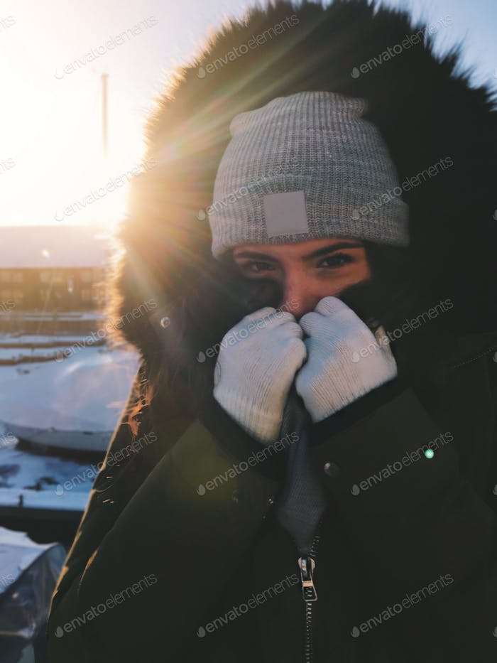 A portrait of a young teenage girl all bundled up covering her face still feeling cold 💲