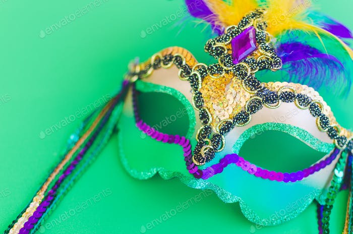 Colorful Mardi Gras mask with feathers on a green background
