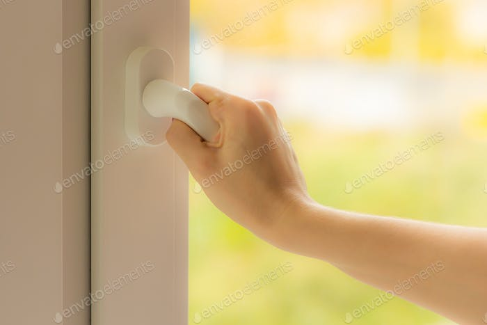 Woman hand opens the window