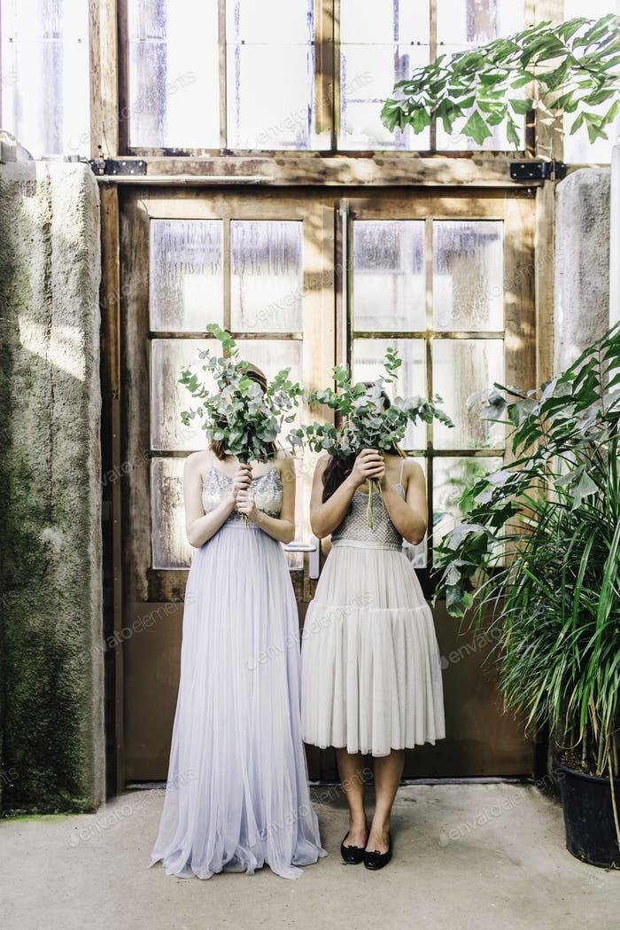 Two Young women in beautiful dresses holding bouquets in front of their heads. Bridesmaids in a bota