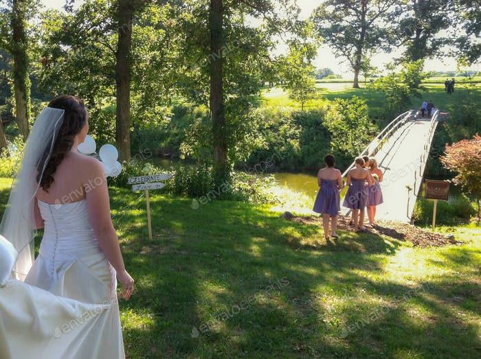 A bride is standing, waiting for her turn in processional at beautiful outdoor wedding