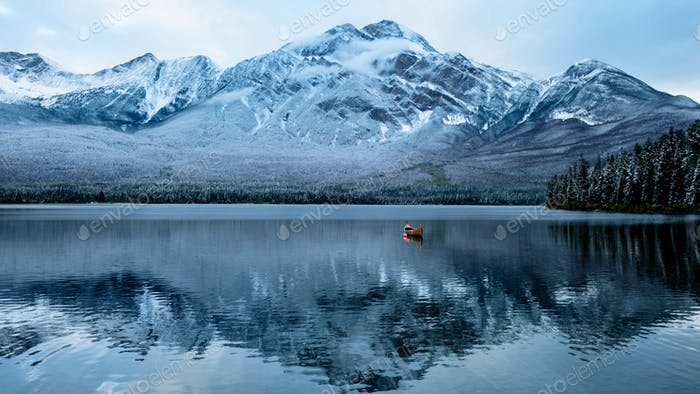A fantastic light show of a lonesome canoe floats on a freezing water lake with surrounding snow