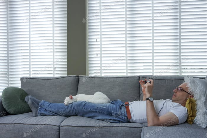Man laying comfortably on the couch at home.