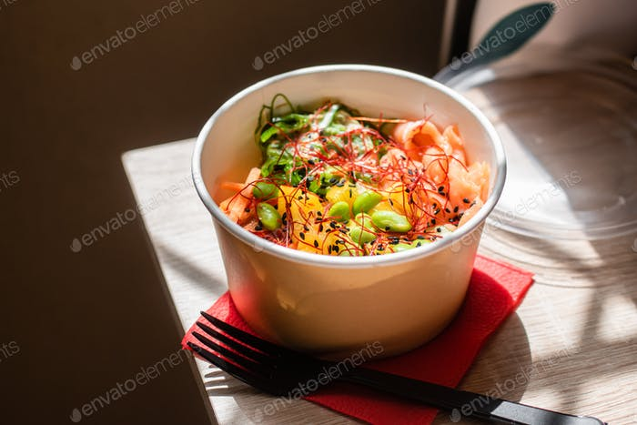 Poke bowl with rice and salmon in craft packaging