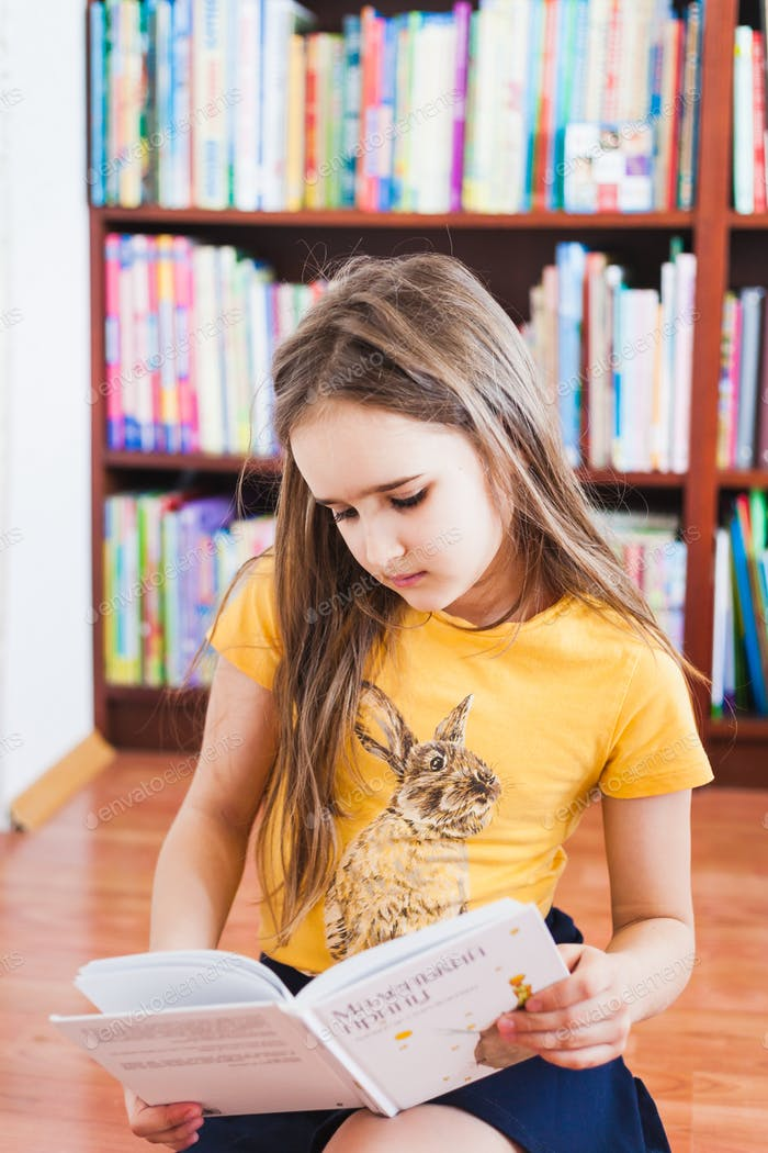 A girl reads a book, title-the Little Prince, author-Exupery, bookcase, learning at home, quarantine